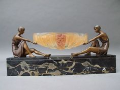 Limousin Table Centre Piece   French bronze patinated spelter ladies mounted on a portorro marble base and holding a pate de verre dish with floral detail