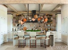 Love this crisp and clean kitchen with exposed stone wall