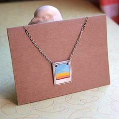 ✋Handmade By Me!✋  This is for our Polaroid sunset / sunrise necklace!   Perfect Gift For Any Occasion!  ❤️All necklaces are hand drawn, colored and printed on durable thick plastic.  ❤️Sealed with acrylic for long lasting color. ❤️Hand strung on a silver chain with lobster clasps!