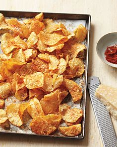 Homemade Potato Chips  To make, spread 4 1/2 cups kettle-cooked potato chips (about 5 ounces, or one large bag) on a rimmed baking sheet. Bake at 350 degrees until oil appears, 6 to 7 minutes. Meanwhile, mix together 1/2 cup very finely grated Parmigiano-Reggiano cheese (about 1 ounce), 1/8 teaspoon paprika, and 1/2 teaspoon cayenne pepper. Remove chips from oven, and immediately sprinkle with cheese mixture. Serve warm or at room temperature. (Serves 4)