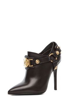 5ce31e8300a18 Step in style with the @Versace black harness bootie with a gold medallion  detail $1,425