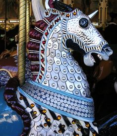 """Victorian carousel at Golden Gate Park, San Francisco, pictured by Judy Watt--""""The spike, rather than to emulate a unicorn, was actually functional, as armoured knight and armoured horse fought as a unit, both equally lethal. This is demonstrated, again, in the large, prominent, teeth of the armoured horses – this is not a friendly grin . . .""""-info from comment posted by Ron-http://squirrelbasket.wordpress.com/2010/09/04/carousel-horses-an-illusion-of-freedom/"""