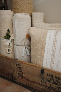 natural fabrics rolled up and stored in basket/wooden crate/old suitcase for decorating a corner. Vintage Accessoires, Old Wooden Boxes, Sweet Home, Old Suitcases, Linens And Lace, White Linens, Textiles, Linen Pillows, Natural Linen