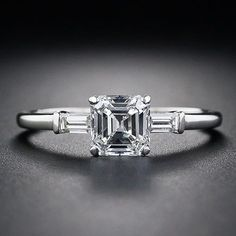 A bright-white and glistening square emerald-cut diamond – sometimes referred to as an Asscher-cut – gleams from between a pair of baguette diamonds in this classic, timeless and traditional estate engagement ring, crafted in platinum, circa 1930s.