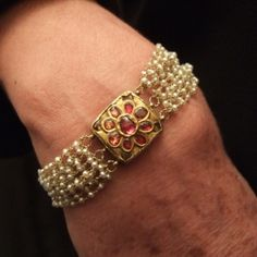 "22ct gold, rubies, freshwater pearls, India Description This type of gold bracelet set with precious stones and refined work is typically moghul.Magnifique design at a time ""solar"" and floral! The Mughal art is art produced in India under the dynasty of the Mughals"