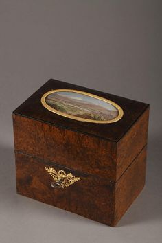 A rectangular wooden box with its key, decorated on the top of the lid with a miniature depicting an aerial view with an ormolu frame finely chiselled with small flowers. The keyhole is decorated with a gilt bronze openwork emblem. The interior of this casket is composed of two compartments for cut-crystal flasks decorated with straight flutes and lattice. The collar and cork mounted in gilt bronze are hightened with water leaves, small flowers, foliages and crowned an angel atop.Circa…