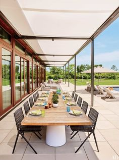 In a Hamptons home by Joe Nahem, chairs by Janus et Cie flank the terrace's custom-made dining table.
