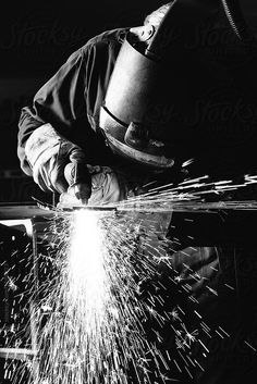 Close up black and white image of steel worker cutting iron with by Urs…