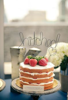 A one-tier naked cake topped with fresh berries and a wire topper, created by Dulce Desserts.: