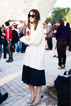 An oversized turtleneck sweater looks amazing with a black midi skirt, pumps and a red clutch.