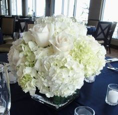 low centerpieces with white hydrangea and blue bella donna. navy blue and silver cuff around the vase