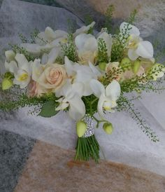 Bridal hand tied bouquet of white orchids and soft pastel roses with diamante cuff.