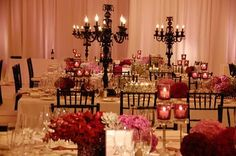 Black Chandeliers with small arrangements and candles at the bottom