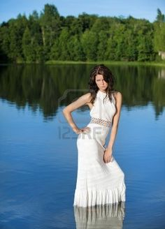 a beautiful brunette posing at a calm lake Stock Photo