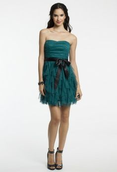 Let the ruffles steal your heart and fall head over heels in love with this short and sweet cocktail dress! The ideal homecoming dress, this short little number is one way to make a grand appearance at the festivity full of your friends. After homecoming and because you love this dress so much also wear it as a holiday dress or even as a guest of wedding dress, every occasion deserves a gorgeous dress like this! A strapless pleated bodice and full ruffle skirt are completed with a pretty ribbon…