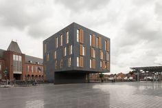 Abscis Architecten - Het passief multifunctioneel gebouw markeert met de grote overkraging ook de toegang tot de ondergrondse parking – fotografie Thomas De Bruyne