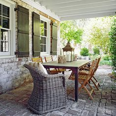 Covered porches flank the entrance, creating a shady place to dine outdoors on a mix of wicker and wood furnishings. Well-worn red brick and a large lantern atop the table cast a nostalgic and serene atmosphere.