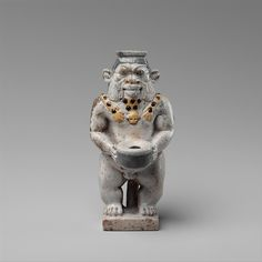 Cosmetic Container in the Form of a Bes-image. Egypt, Late Period, 525–404 B.C. Faience, h. 9.2 cm (3 5/8 in). The god stands holding the cap of a kohl container, which has a small round hole in the top for insertion of an applicator. I Metropolitan Museum