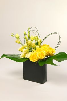 Geometric floral design in a black ceramic vase with yellow roses and
