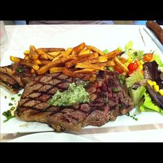 Perfectly cooked medium rare steak frite with herb butter and side salad, enough for 2.