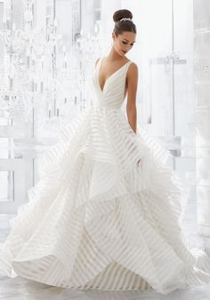 """Light and Airy, this Stunning Flounced Organza Ball Gown with Wide Horsehair Edging Features a Plunging V-Neck and Open V-Back. Illusion Insets Along Sides . Available in Three Lengths: 55"""", 58"""", 61"""". Colors Available: White, Ivory, Ivory/Stripe."""