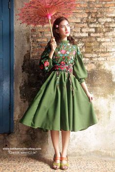 Batik Amarillis made in Indonesia  Batik Amarillis's Ildiko dress  in beautiful  & extravagant Polish embroidery this 70ies inspired dress  oozing romanticism with this full circle  skirt,beautiful puff sleeves , tassel belt and each details lends the style an ethereal charm.