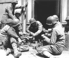 Eight U.S. soldiers preparing to lunch at the entrance of a house.