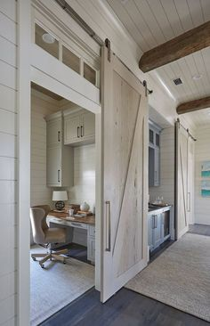 One of the pecky cypress barn door opens to reveal a home office with light gray cabinets suspended over a gray built-in desk with wood top. Barn doors are painted in a custom whitewash stain. ideas Florida Beach House with New Coastal Design Ideas Home Design, Luxury Interior Design, Blog Design, Interior Modern, Light Gray Cabinets, Wood Cabinets, Built In Desk, Built Ins, Cool Ideas