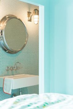 Coastal Living Showhouse - Nautical turquoise blue kid's bathroom features walls clad in turquoise blue penny tiles by Ann Sacks lined with a Restoration Hardware Royal Naval Porthole Mirrored Medicine Cabinet and a wall mount faucet and wall mount sink illuminated by cage sconces.