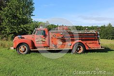 An old red firetruck parked on a grassy field.