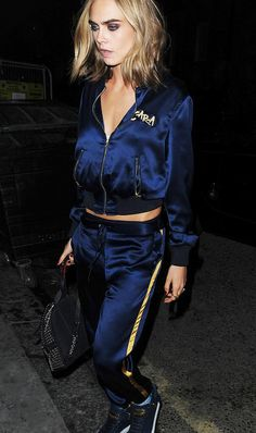Cara Delevingne in London wearing a monogrammed tracksuit.