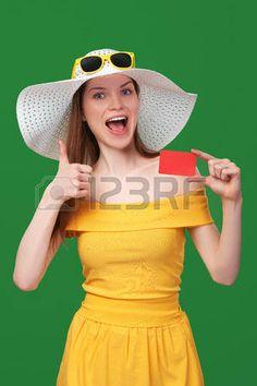 La mujer del verano sorprendido emocionada en vestido de verano de color amarillo y un sombrero. Fondo verde.