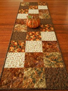 Beautiful bronzed orange pumpkins and turning autumn leaves are all highlighted with metallic gold accents in this quilted fall table runner. Five different prints were used, in rich shades of the season - browns, rust, bronze and bits of green. The size is approximately 14 X 44 (36 X 112 cm) - a versatile size for use on a dining table, buffet, coffee table or a bedroom dresser. I machine-quilted an all-over meander with a variegated rayon thread in shades ranging from cream to gold to…