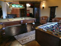 Outside of the in-home theater is this game room. The antique pool light adds a nice touch for the pool table, when you playing pool it is just like playing in an old bar from back in the day.  Next to the pool table is a Foosball table that is super exciting to play.  Notice the entry way to the in-home theater. The doors are antique Chinese temple doors and the roof top is actually from an old building.