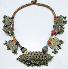 India - An old silver amulet pendant is strung on colourful yarn with six silver pendants. Silver alloy, exact silver content unknown.