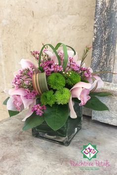 Leaf lined cube with cymbidium orchids and premium green accents.