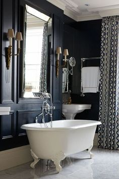 Black Paneled Bathroom with White Claw Foot Tub and Twin Pedestal Sinks