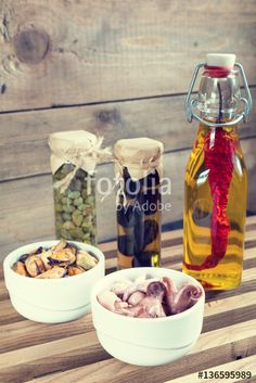 "Download the royalty-free photo ""Octopus in ceramic bowls and bottle of olive oil with chili pepper. Mussels in ceramic bowls, black olives and capers in jar, bran bread on black stone board. Mediterranean food"" created by Victoria Kondysenko at the lowest price on Fotolia.com. Browse our cheap image bank online to find the perfect stock photo for your marketing projects!"