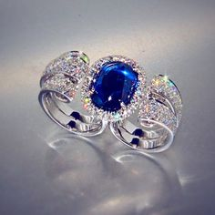Paso Doble: an oval cabochon cut Burma sapphire rests on a structure of gold and…