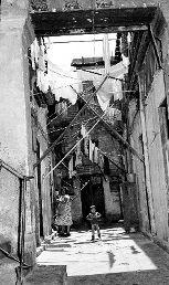 1930 Mujer en la azotea de una vivienda señalando algo.