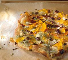 Kürbis-Gorgonzola-Flammkuchen: Der im Elsass beheimatete Flammkuchen besteht aus einem dünnen Hefeteigboden und wird nach Herzenslust belegt. Hier mit Kürbis, Gorgonzola, Nüssen, Cranberries und Rosmarin.