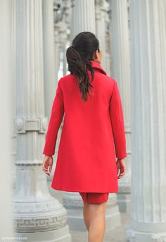 LA Urban Lights -- Boldly popped in a vibrant shade of red, this must-have is the luxe coat of the season, flaunting a dramatic funnel neck for a couture-worthy silhouette. Styled by Extra Petite. Featured at LACMA in Los Angeles.