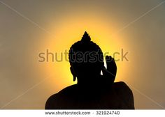 Buddha statue with dark silhouette with golden orange sunlight glowing on head with peace (ok) hand sign