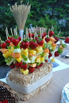 Fruit skewers on a hay bale...a delicious way to add color to your Mother's Day Garden Brunch table! See how we displayed ours and what we served them with in this clip at http://www.youcanplanaparty.com/planning/food-a-beverage/140-food-a-beverage-mothers-day-garden-brunch.html.