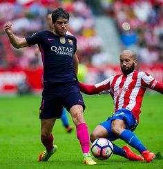 Sergi Roberto Carnicer of FC Barcelona duels for the ball with Alberto Lora of Real Sporting de Gijon during the La Liga match between Real Sporting...