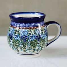 """Skillfully created in Boleslawiec, Poland this hand-made and hand-painted mug displays its many artistic qualities. For centuries, Polish Pottery has been crafted with beautiful and unique designs, and this Polish Pottery set continues this tradition with versatile pieces that are perfect for mixing and matching. Signed by the artist.DetailsMaterialStonewareCapacity12 ozDimensions3.25"""" W x 3.625"""" HCare InstructionsDishwasher safe. Microwave safe.Country of OriginPoland"""