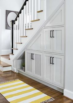 Yellow and gray foyer features under the stairs pull out cabinets alongside a yellow striped runner with fringe trim.