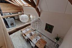 Kijkje vanuit de vide naar beneden. Speksteenkachel die bijna het hele huis verwarmt. #TeKoop - unieke woonboerderij Meerlo