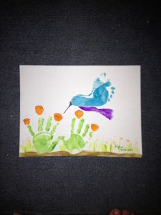 Footprint hummingbird with handprint flowers.