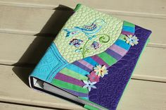 A quilted photo album cover made on the Bernina 780 using improvisational piecing, couching, Cutwork, and embroidery.  http://amandamurphydesign.blogspot.com/2012/12/the-bernina-780-improvisational-photo.html